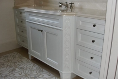 Guest room bathroom cabinetry in white.
