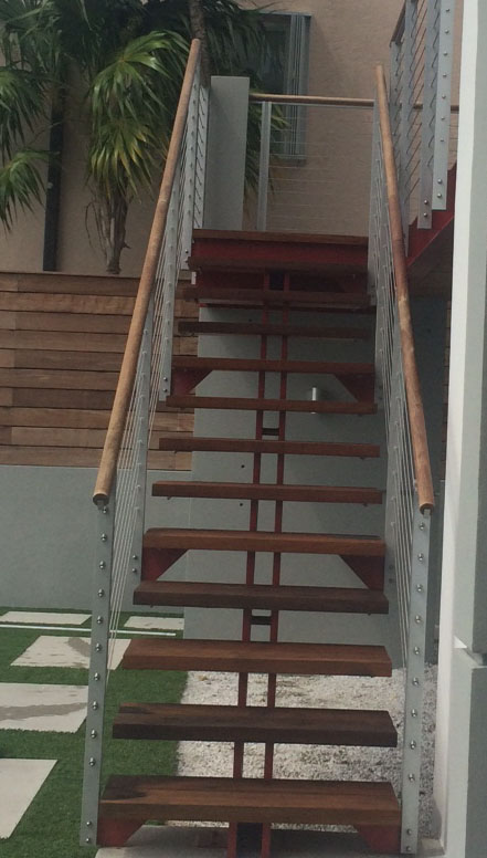 Beautiful staircase and balconies made out of ipe wood surround the home.